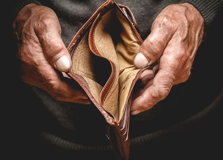 Empty wallet in the hands of an elderly man. Poverty in retirement concept Stock Photo