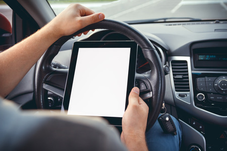 concep: A young man with a tablet in his hand at the wheel of the car. Multitasking. Safe driving concep