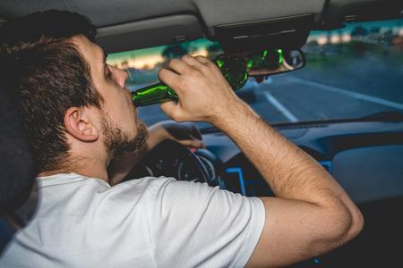 borracha del hombre joven que conduce un coche con una botella de cerveza. No beber y concepto de accionamiento. Conducir bajo la influencia. DUI, conducción en estado de embriaguez. DWI