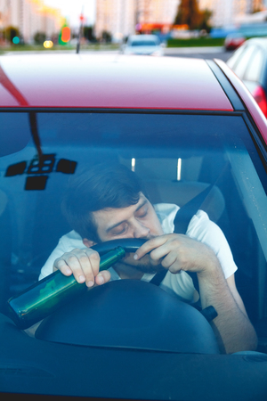 dui: Drunk young man driving a car with a bottle of beer. Dont drink and drive concept. Driving under the influence. DUI, Driving while intoxicated. DWI