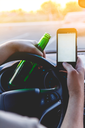drink and drive: Drunk young man driving a car with a bottle of beer and mobile phone. Dont drink and drive concept. Dont text and drive. Driving under the influence, Driving while intoxicated.