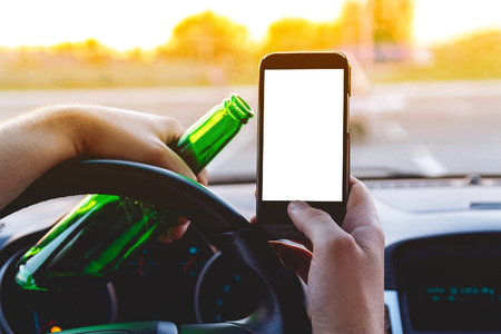 under the influence: Drunk young man driving a car with a bottle of beer and mobile phone. Dont drink and drive concept. Dont text and drive. Driving under the influence, Driving while intoxicated.