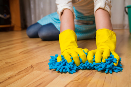 floor cloth: Wash wood floor concept. Young woman wipes the floor with a cloth gloves, sitting on his lap