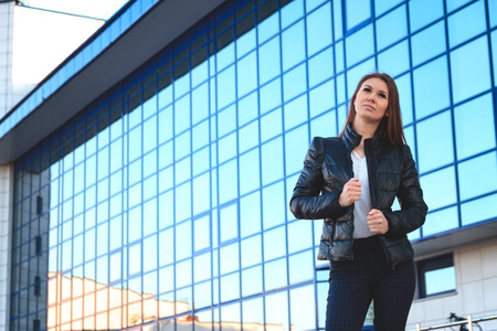 informal: Portrait of a beautiful young lady in beznes informal dress on a background of the business center. The informal business, free business concept