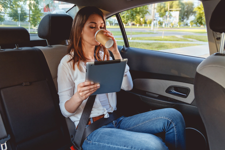 Jonge, mooie vrouw zit in de achterbank van de auto met een tablet in de hand en drinken koffie