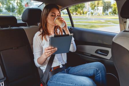 Joven, bella mujer sentada en el asiento trasero del coche con una tableta en la mano y el consumo de café