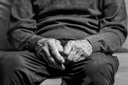 The old, wrinkled hands of an elderly man close up. Senior sitting on a sofa