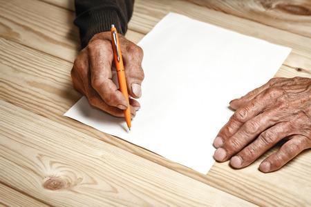 testament schreiben: Der alte Mann hat ein Testament, an einem Holztisch sitzen Lizenzfreie Bilder