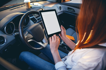 safe driving: Young, beautiful woman driving a car with a tablet in hands. Back view. Safe driving concept. Multitasking Stock Photo
