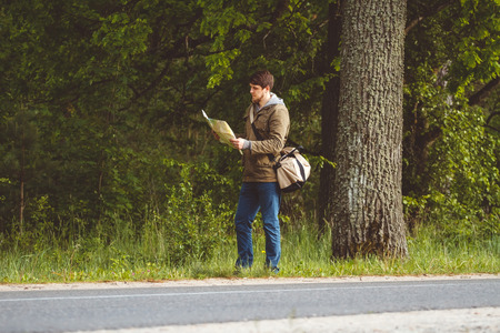 hitchhiking: Man with map and bag in hand walking on a roadside. Hitchhiking concept