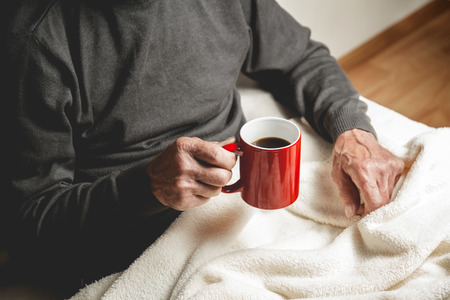Elderly man sitting on the couch with a cup of coffee in hand
