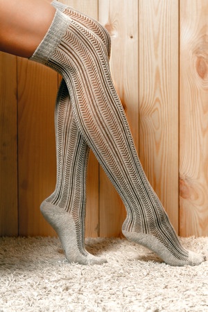 shapely legs: Beautiful, shapely female legs in brown knitted, warm stockings, standing on the carpet