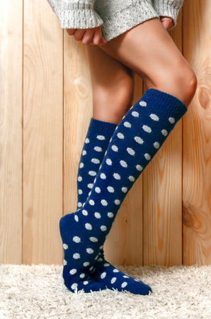 shapely legs: Beautiful, shapely female legs in gray knitted sweater and warm blue stockings standing on carpet