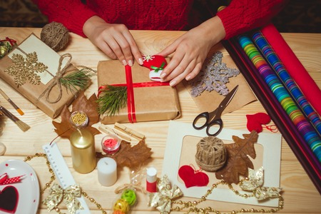 Girl sits at the table wraps Christmas presents. Handmade Stock Photo