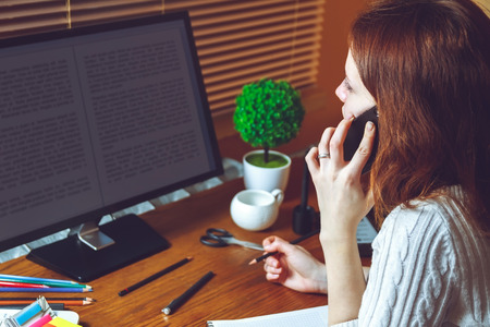 telework: Young business woman talking on the phone while sitting at the table. Multitasking concept. Telework concept