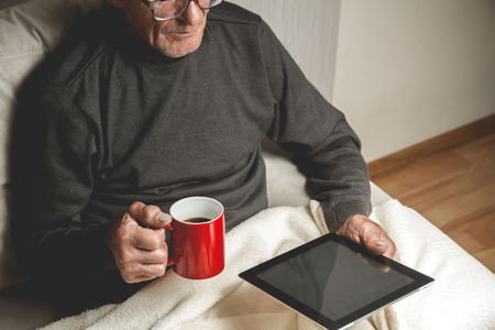 teleworking: Senior with spectacled sitting on the couch with a tablet  and red cup of coffee in hands. Online education retirement concept. e-Learning. mock up