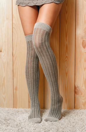 shapely legs: Beautiful, shapely female legs in lace sweater and brown knitted, warm stockings, standing on the carpet Stock Photo