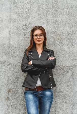 leather belt: Portrait of a beautiful girl in jeans and a black leather jacket from the concrete wall