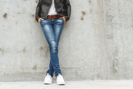 shapely legs: Shapely female legs in sneakers and jeans near a concrete wall