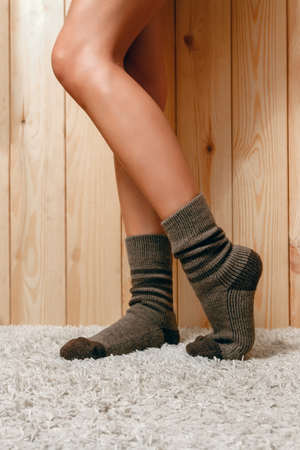 shapely legs: Beautiful, shapely female legs in brown knitted, warm socks with dark stripes