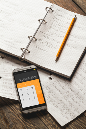 exponential: Solving mathematical problems in a notebook .  Phone with calculator app on wooden desk.