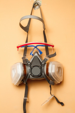 absorption: Mask respirator and goggles on the wall. Copy space
