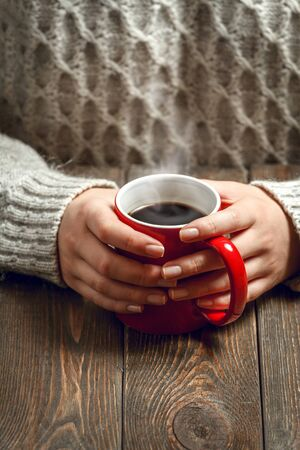 black sweater: The girl in a cozy knitted sweater drinking coffee from a red mug, sitting at a vintage wooden table