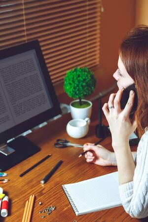 says: Young business woman talking on the phone while sitting at the table. Multitasking concept. Telework concept