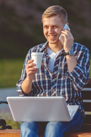 distant work: A young male businessman with a laptop and telephone. Remote work outdoors Stock Photo