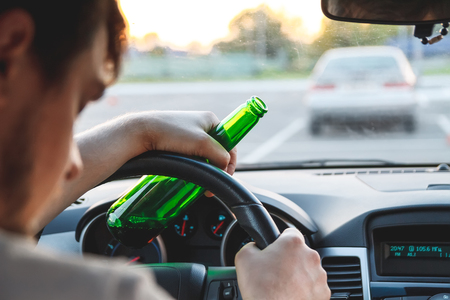 Drunk young man driving a car with a bottle of beer. Dont drink and drive concept. Driving under the influence. DUI, Driving while intoxicated. DWI