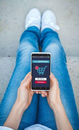 Dziewczyna robi zakupy w sklepie internetowym za pomocą telefonu komórkowego. Koncepcja zakupów online