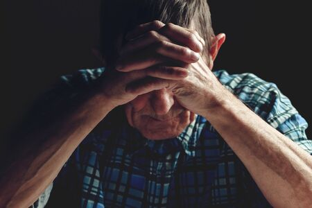 Depressed elderly man covers his face with his hands. Alzheimers disease concept.