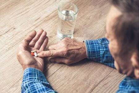 Seniors hands, a glass of water and pills are lying on the table. Painful old age. Health Care for the Elderly