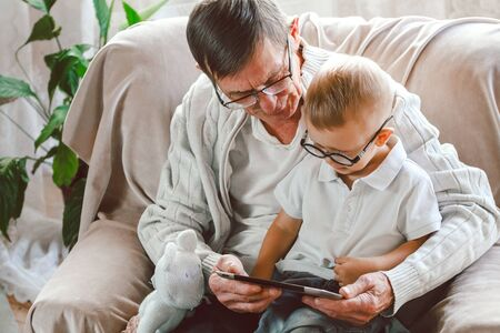 An elderly grandfather and his little grandson are using a tablet device together, smiling and having fun or watching a funny video on the Internet, sitting in a chair Zdjęcie Seryjne