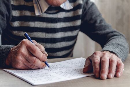 Elderly man solves sudoku or a crossword puzzle to slow the progression of Alzheimers disease
