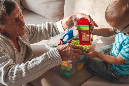Elderly grandfather plays with his little grandson with plastic blocks