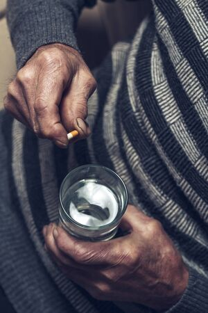 An elderly man takes pills with a glass of water. Painful old age. Retirement care. Alzheimers Disease Prevention