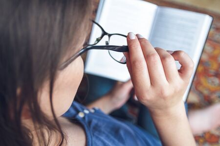 A woman with vision problems is reading a book with glasses. Eye fatigue concept