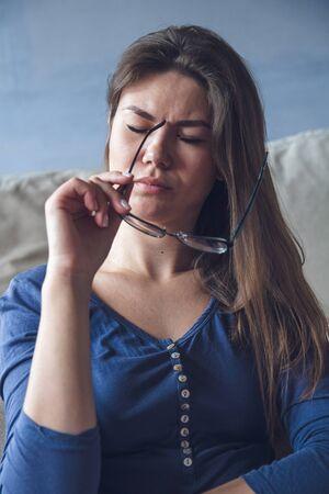 Une femme ayant des problèmes de vision lit un livre avec des lunettes. Notion de fatigue oculaire