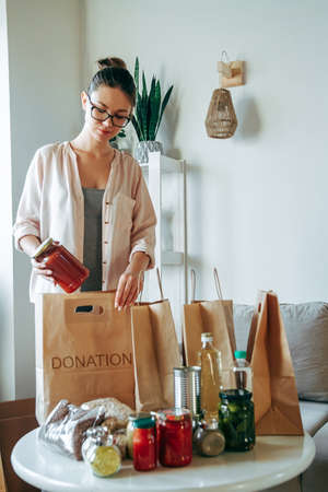 Woman packing food for donation in paper bag with copy space for blank