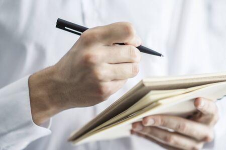 Der Mensch macht Notizen in einem Notizblock. Nahaufnahme