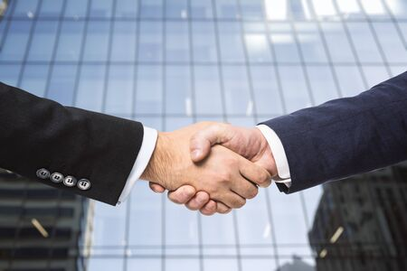 Two businessmen shake hands on the background of the exterior of an office building. Partnership concept