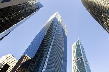 Modern skyscrapers in a financial district at sunset, looking up perspective, real estate and success concept, USA