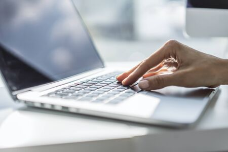 Female hands typing on laptop keyboard in sunny office, business and technology concept. Close up