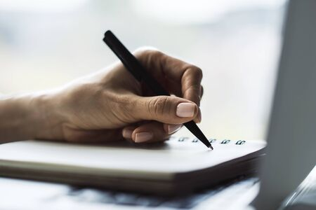 Businesswoman writes with a pen in diary on laptop keyboard in a sunny office, business and education concept. Close up Foto de archivo