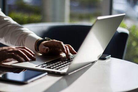 Man working with laptop keyboard and digital tablet in sunny office, business and technology concept. Close up