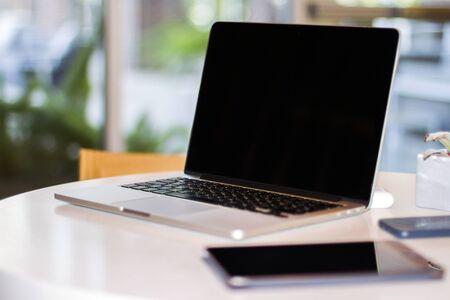 Nahaufnahme eines modernen Laptops mit leerem Bildschirm auf weißem Tisch im sonnigen Interieur, Modell. Geschäfts- und Technologiekonzept Standard-Bild