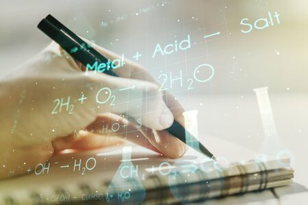 Creative chemistry concept with woman hand writing in notebook on background. Multiexposure