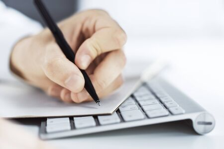 Man writes with a pen in notepad on laptop keyboard in a sunny office, business and education concept. Close up Foto de archivo