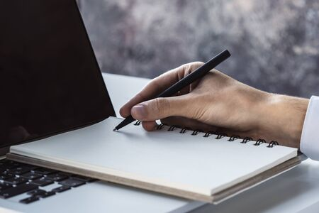 Man writes with a pen in diary on laptop keyboard in a sunny office, business and education concept. Close up